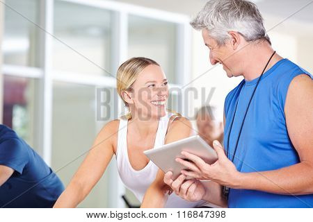 Fitness trainer with tablet PC talking to smiling woman in a gym