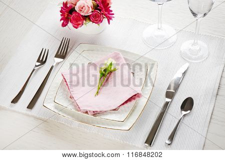 Table setting with dishes, cutlery and flowers on white background