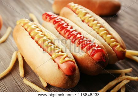 Hot dogs with fried potatoes on wooden background