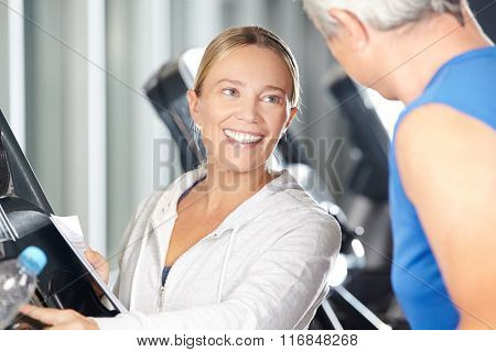 Female fitness trainer helping senior on treadmill in a fitness center