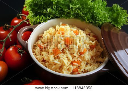 Stewed rice with a carrot and tomatoes in a cooking pot over black background, close up