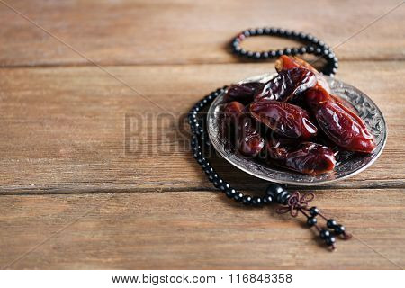 Dates fruit and rosary on wooden background, close up