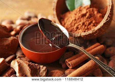 Aromatic cocoa harvest with tasty chocolate on wooden background, close up