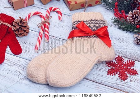 Composition of warm socks and gloves with Christmas decorations on white wooden background