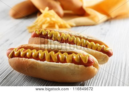 Hot dogs with cheese on wooden background