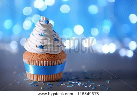 Cupcake with white cream icing on a glitter background, close up