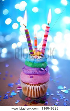 Cupcake with varicolored cream icing and candles on a glitter background, close up