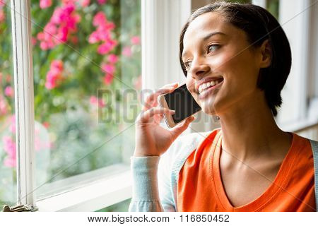 Smiling brunette on a phone call near the window
