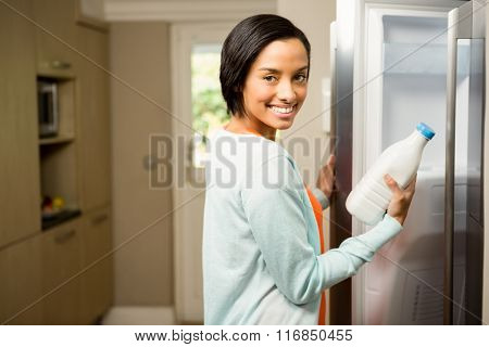 Smiling brunette holding milk bottle with open refrigerator in the kitchen