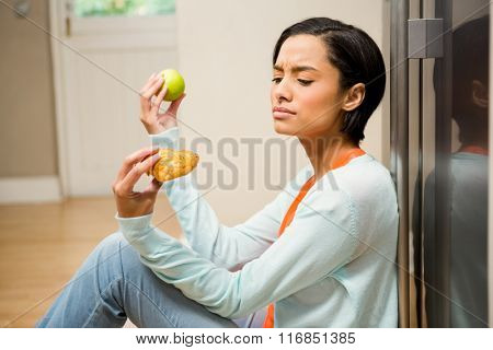 Unsettled brunette holding apple and dessert sitting on the floor in the kitchen