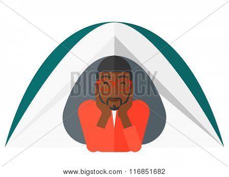 Man lying in tent.