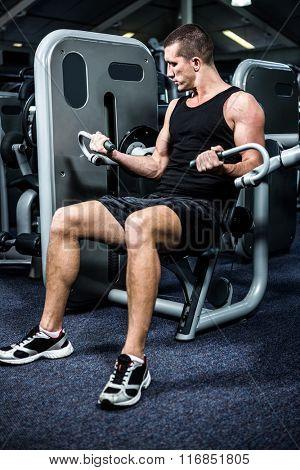 Serious muscular man using exercise machine at gym