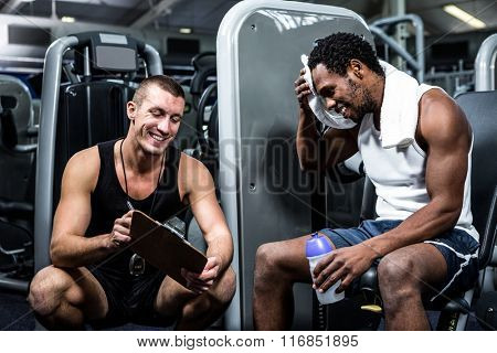 Muscular man discussing performance with trainer at gym