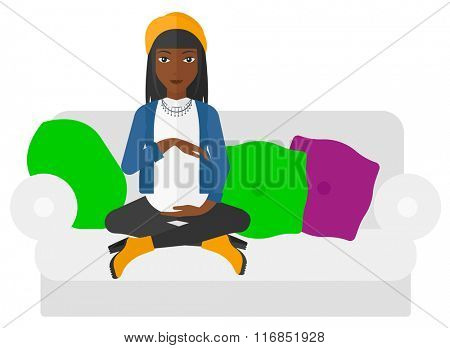 Pregnant woman sitting on sofa.