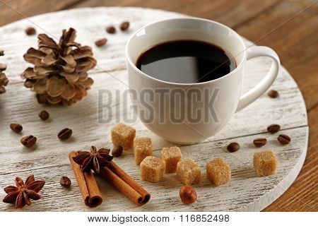 Cup of coffee with sugar and cinnamon on white wooden mat