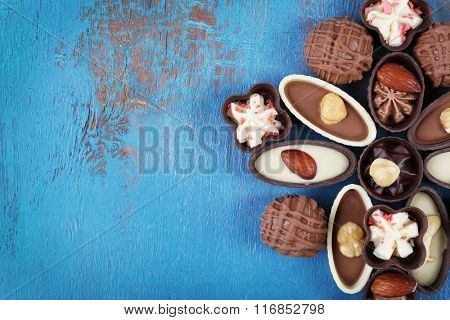 Chocolate sweets on old blue wooden background, top view