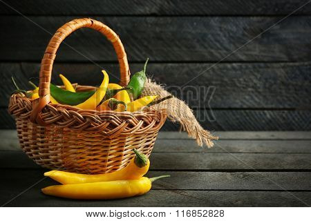 Chili peppers in wicker basket on  wooden background