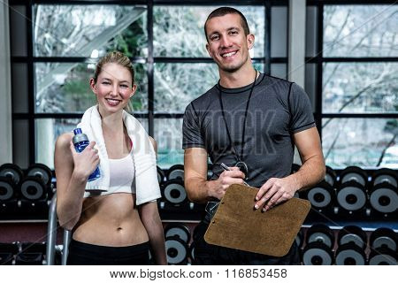 Male trainer and fit woman smiling at gym