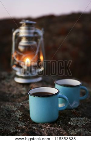 Decorative lamp and two blue mugs on rock in mountains