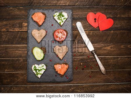 Mini Canapes Heart Shape With Different Toppings On Black Slate Board, Vintage Knife And Two Red Hea