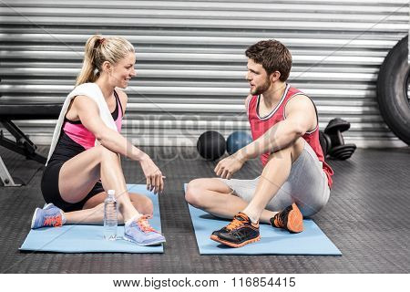 Couple sitting and talking together at crossfit gym
