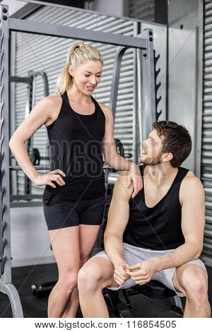 Fit couple talking together at crossfit gym