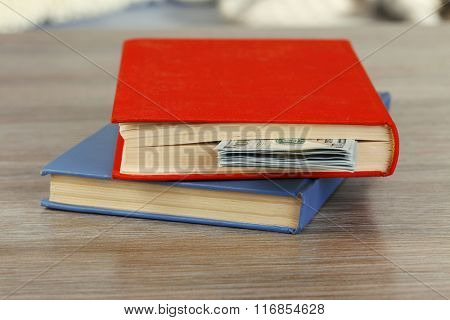 Red and blue books with hidden dollar banknotes on wooden table