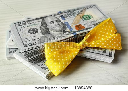 Dollars and colorful bow on light background