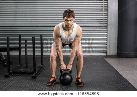 Fit man lifting dumbbells at crossfit gym