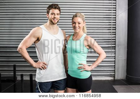 Fit couple posing together at crossfit gym