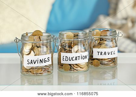 Glass jars with Ukrainian coins for savings, education and travel on a table