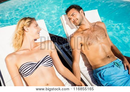 Cute couple relaxing on deckchairs by the pool
