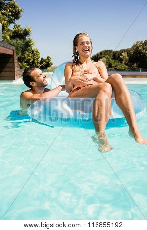 Happy couple in the pool with lilo in a sunny day