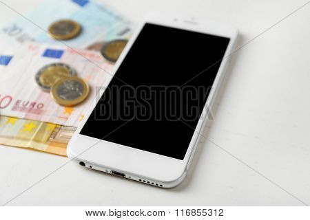 Smart phone and euro banknotes with coins on light table. Telephone charges