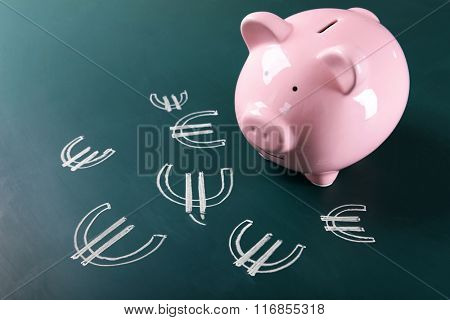 Piggy bank on chalkboard with Euro currency symbols