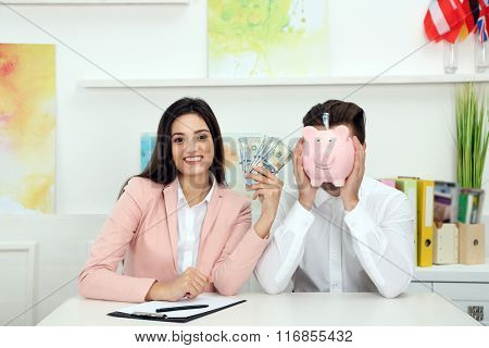 Happy young couple with dollar banknotes and piggy bank. Money savings concept
