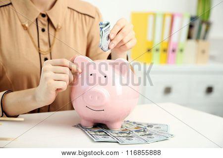Woman putting dollar banknotes into piggy bank. Savings money concept
