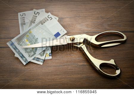 Golden scissors cut money on wooden background