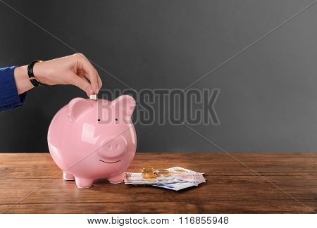 Woman putting coin in pig moneybox