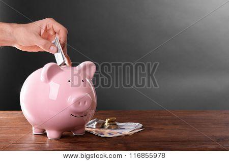 Man putting money in moneybox