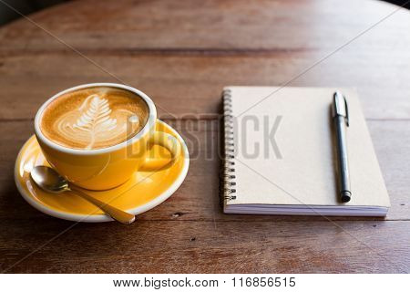 Hot Latte Art Coffee Cup On Wooden Table And Note Book.
