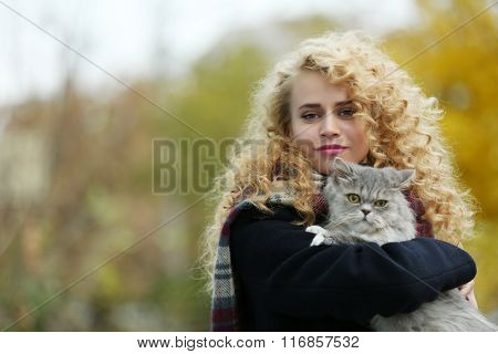Young woman and cat in the park