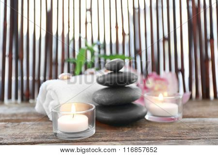 Spa stones with towel, candles, bamboo and pink orchid on wooden background