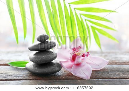 Spa stones with palm leaves and pink orchid on wooden background