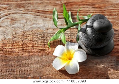 Spa stones with bamboo and tropical flower on wooden background