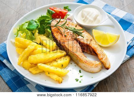 Fried salmon with French fries and vegetables