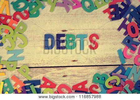 Debts Word Block Concept Photo On Plank Wood