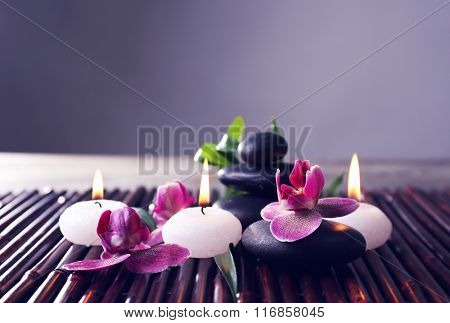Spa still life with beautiful flower and candlelight on grey background