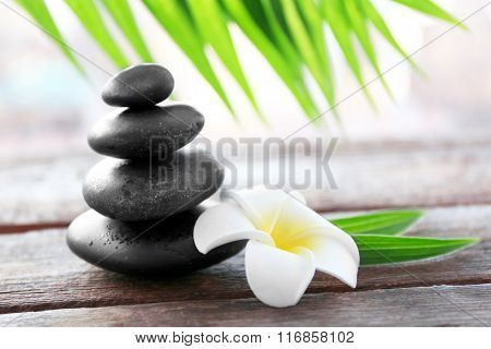 Spa stones with bamboo, palm leaves and tropical flower on wooden background