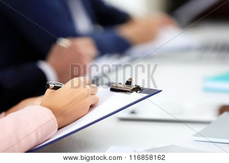 Woman's hand making notes at the business meeting